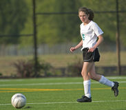 Soccer Girl varsity 5e. High School girl varsity soccer player with the ball on a turf field Royalty Free Stock Image