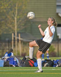 Soccer Girls varsity 3. High School girls varsity player controlling the ball with her knee Stock Photo