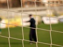 Soccer goal net. Soccer player on pitch seen through football goal net royalty free stock photos