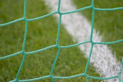 Soccer goal net. Closeup view of a green soccer goal net against a background of grass and a white line Stock Photos