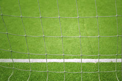 Soccer goal net closeup background. Soccer goal net closeup with blurred soccer field background. Selective focus used Royalty Free Stock Photography