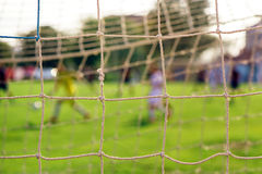 Soccer goal net. With players in defocussed background Royalty Free Stock Photo