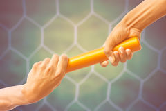 Soccer goal net vintage background. Hands passing a relay baton on on soccer goal net background with vintage color tone effect Stock Photography