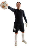 Soccer goalie. Football goalkeeper in black blouse and shorts wearing goalie gloves. Man is holding ball in right hand. Studio shot on white background Royalty Free Stock Images