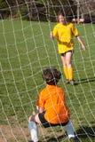 Soccer Goalie. Girl kicking ball at soccer field practice in goalie pen Stock Photo