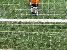 Soccer goalie boy. Abstract view of a child soccer goalie from the waist down, through the goal net from behind and above Royalty Free Stock Photos