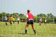 Soccer Goalie Ready for Attack. Female soccer goalie readies for attack, perspective from behind goal netting Royalty Free Stock Image