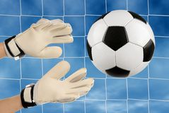 Soccer goalie's hands in action. Soccer goalkeeper's hands reaching for the ball, with net and sky in the background stock photography