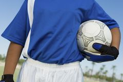 Soccer goalkeeper (13-17) holding ball. Mid section stock image