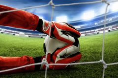 Soccer goalkeeper catches the ball. On the field stock images