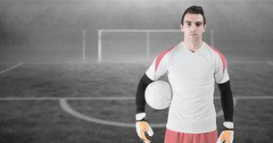 Soccer goalkeeper holding football. Digital composite of Soccer goalkeeper holding football stock image