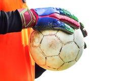 Soccer goalkeeper holding old soccer ball with gloves.. Stock Image