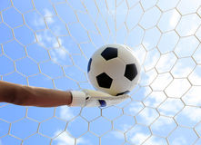 Soccer goalkeeper's hands reaching for the ball Royalty Free Stock Images