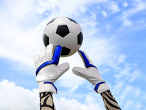 Soccer goalkeeper's hands reaching for the ball Royalty Free Stock Photography