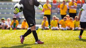Soccer Goalkeeper Throw. Football Training Game for Kids. Young Boy as a Football Goalkeeper Standing in a Goal. Soccer Players in the Background. School royalty free stock image