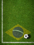 Soccer grass field corner with ball and flag of Brazil Stock Photo