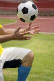 Soccer'hands que alcanza la bola del pie Fotos de archivo libres de regalías