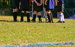 Soccer huddle. Kids' soccer team in coach's huddle Royalty Free Stock Photo
