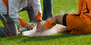 Soccer injured. Lying down on the grass with doctor Stock Image