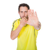 Soccer judge whistling and showing stop sign Royalty Free Stock Image
