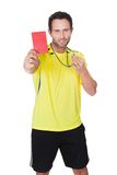 Soccer judge whistling and showing yellow card Stock Photo