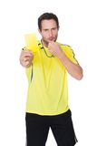 Soccer judge whistling and showing yellow card Royalty Free Stock Photos