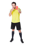 Soccer judge whistling and showing yellow card Royalty Free Stock Image