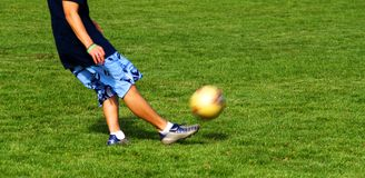 Soccer Kick 1. A person kicking a soccer ball across the field Stock Photos