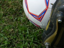 Soccer kick. Foot on a soccer ball in the grass Royalty Free Stock Photos