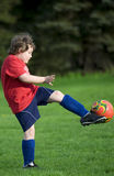 Soccer Kick. Young soccer player doing big kick during game Royalty Free Stock Images
