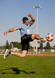 Soccer kick. Athletic male in the air kicking a soccer ball