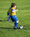 Soccer Kick Off. Young soccer player kicking to start game Royalty Free Stock Photography