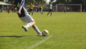 Soccer Kick. A young male soccer player takes a kick out from the goal square Royalty Free Stock Photos