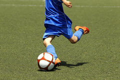 Soccer Kids. Little boy shooting a ball during a soccer match Stock Photo