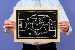 Soccer manager with strategy. Body of soccer of football manager holding winning strategy diagram on blackboard on chalkboard stock photos