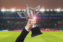 Soccer manager team holding trophy champions in the stadium. Royalty Free Stock Images