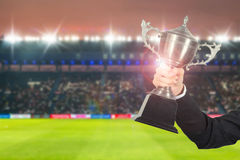 Soccer manager team holding trophy champions in the stadium. Stock Image