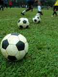 Soccer match and balls. Soccer match in front of an arrangement of 3 footballs Royalty Free Stock Photos