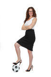 Soccer Mom in High Heels. Smiling woman in heels, black skirt and white blouse with arms folded and one foot on a soccer ball Royalty Free Stock Image