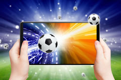 Soccer online. Abstract tablet pc in hands, soccer ball on screen, multimedia gadget, soccer, football online Royalty Free Stock Photo