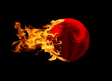 Soccer out of Hell. A red metallic soccer ball with fire tail comet like on a black background Royalty Free Stock Photo