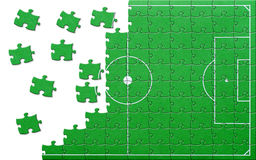 Soccer pitch jigsaw puzzle. Overhead view partially completed football or soccer pitch jigsaw; isolated on white background vector illustration