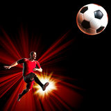 Soccer player. Kicking the ball in to the air Stock Image