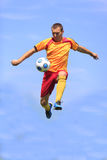 Soccer player. Kicking the ball while jumping Stock Photo