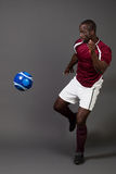 Soccer Player. Male soccer player. Studio shot over grey Royalty Free Stock Photo