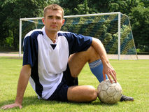 Soccer player. Sitting on a field in front of a goal net stock photos