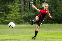 Soccer player. Kicking a ball stock photography