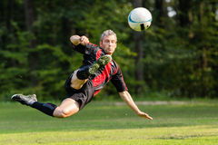 Soccer player. Kicking a ball in a bicycle kick stock images
