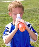 Soccer Player. Young sweaty red faced boy taking drink at halftime of soccer game Royalty Free Stock Image