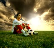 Soccer player. A soccer player sitting on the field Royalty Free Stock Image